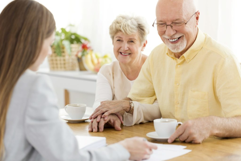 Elderly couple signing life insurance contract